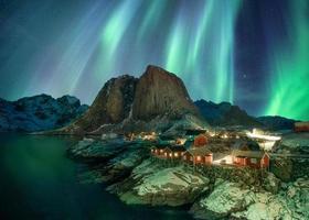 Northern lights over fishing village with mountain range on coastline at Hamnoy photo