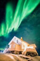 Aurora borealis Northern lights over white house illuminated on snowy in winter photo