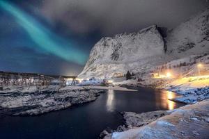 Scandinavian village illumination with northern lights shining on snow mountain photo