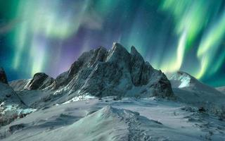 Aurora borealis over majestic mountain in snowy on Segla Island photo