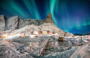 Landscape of snowy mountain with aurora borealis in scandinavian village photo