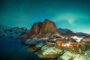 Aurora borealis over mountain with fishing village at Hamnoy photo