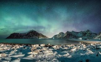 Aurora borealis with stars over mountain range with snowy coastline at Skagsanden beach photo