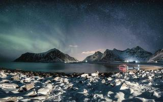 Aurora borealis with milky way over snow mountain on coastline photo