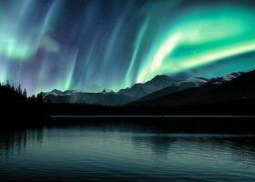 Aurora boreal, auroras boreales sobre las montañas rocosas canadienses en el bosque en el lago piramidal en el parque nacional jasper foto
