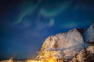 Aurora borealis over snow mountain in Reine town at Lofoten Islands photo