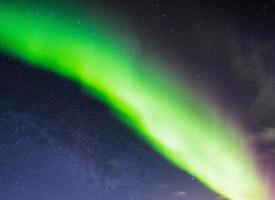 Northern lights or Aurora borealis in the night sky over arctic circle in Scandinavia photo