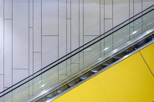 Beside yellow escalator with lighting on wall photo