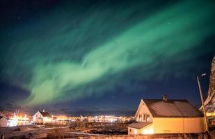 Aurora borealis dancing over scandinavian village photo