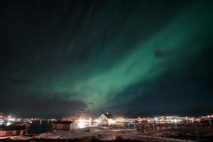 Northern lights, Aurora borealis over scandinavian village on coastline at Lofoten Islands photo