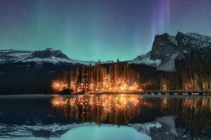 Lodge de madera iluminado con la aurora boreal en el lago esmeralda en el parque nacional yoho foto