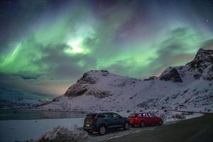 Cars parking on country road with northern lights on sky at Lofoten photo