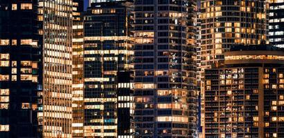 Ventanas de la fachada del rascacielos moderno iluminado con edificio de oficinas en la noche foto