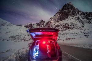 Man tourist sitting on rear car in mountain surrounded with aurora borealis photo