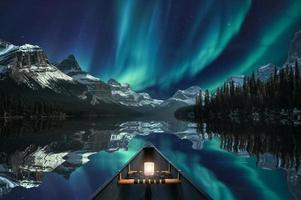 Canotaje con aurora boreal sobre la cordillera en el lago maligne en el parque nacional jasper foto