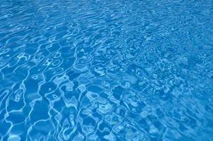 Superficie ondulada de agua azul en la piscina foto