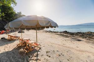 Umbrella with wooden sunbed on the white beach at tropical sea photo