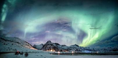 Northern lights explosion on snowy mountain range photo