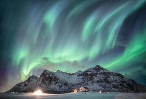 Aurora borealis with starry over snow mountain range with illumination house in Flakstad, Lofoten islands, Norway photo