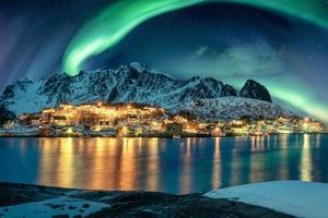 Aurora borealis over fishing village illumination on coastline in winter at Lofoten Islands photo