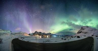 Aurora borealis with starry over mountain range on arctic coastline photo