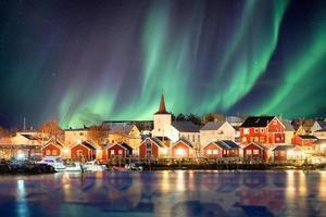 Iglesia cristiana en pueblo de pescadores brillando con la explosión de la aurora boreal foto