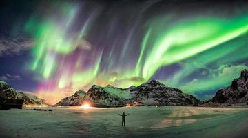 Aurora borealis, Northern lights over mountain with one person photo