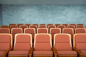 Row of brown theatre seats and marble wall in auditorium photo