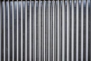Vertical aluminium fence on concrete wall background photo
