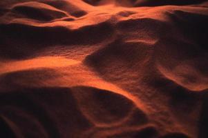 Arena brillante ondulada del desierto al atardecer foto