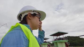 Female engineer in a white helmet and yellow uniform holds a blueprint and looking away at the dam construction site to generate electricity. video