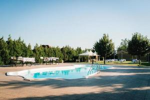 blue outdoor pool in the garden surrounded by trees photo