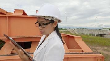 Female engineer in a white helmet holds a digital tablet and using radio communication at the dam construction site to generate electricity. Clean energy and Technology concepts. video