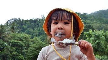 menina bonitinha comendo sorvete ao ar livre em um dia quente de verão. video