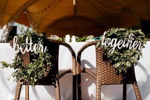 el presidium de los recién casados en el salón de banquetes del restaurante está decorado con velas y plantas verdes, el tono general del salón es beige foto