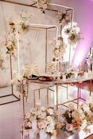 the presidium of the newlyweds in the banquet hall of the restaurant is decorated with candles and green plants, the general tone of the hall is beige photo