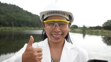 Female engineer in a helmet looks and smiles at the camera while holding a digital tablet with her thumb up at a dam construction site to generate electricity. video