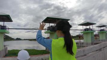 ingénieure portant un casque blanc et un uniforme jaune portant des lunettes de réalité virtuelle à casque vr imaginant la future construction d'un barrage pour produire de l'électricité sur le chantier de construction. video