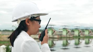 ingénieure dans un casque blanc utilisant la communication radio avec un travailleur sur le chantier de construction du barrage pour produire de l'électricité. video