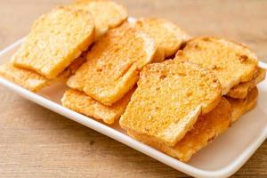 Baked crispy bread with butter and sugar on plate photo