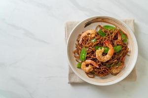 fideos yakisoba salteados con guisantes y camarones - estilo de comida asiática foto