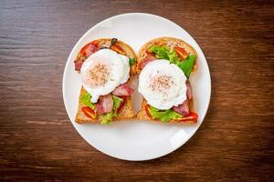 Whole wheat bread toasted with vegetable, bacon, and egg or egg benedict, for breakfast photo