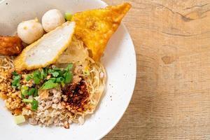 fideos picantes con bola de pescado y carne de cerdo picada o fideos tom yum - estilo de comida asiática foto