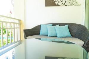 Cómoda decoración de almohadas en una silla de patio en el balcón foto