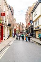 York, Yorkshire, United Kingdom - SEP 3, 2019 - Stonegate street is one of the oldest streets in York with some of the half-timbered buildings. Tourists visiting and shopping in Stonegate street. photo