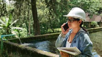 ecologista feminina com chapéu de segurança trabalhando e controlando a qualidade da água na estação de tratamento de águas residuais. engenheiros ambientais trabalhando em usina de reciclagem de água para reutilização. video