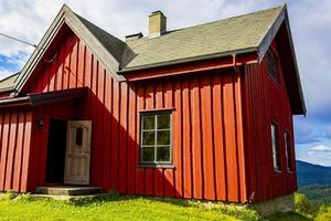 Beautiful red wooden cabin hut on hill in Norway nature. photo