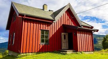 Hermosa cabaña de madera roja en la colina en la naturaleza de Noruega. foto