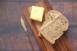 Slice of butter and whole meal bread on chopping board photo