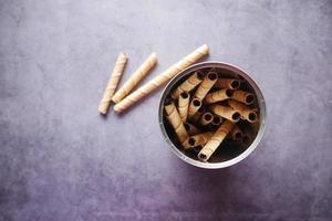 Rollo de obleas de chocolate en un recipiente sobre fondo negro foto